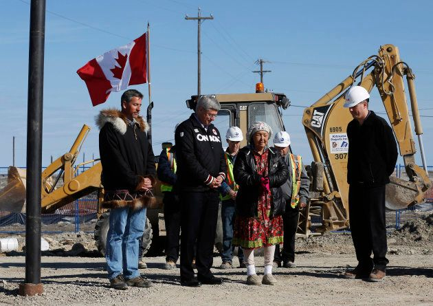 Former Canadian Prime Minister Stephen Harper, second from left, listens as elder Eva Otokiak, second...