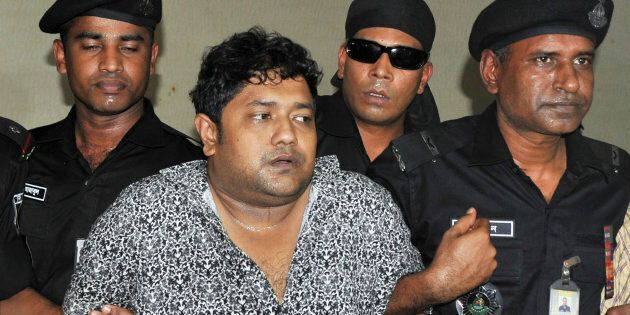 Members of the Rapid Action Battalion (RAB) present Mohammed Sohel Rana to the media after his arrest...