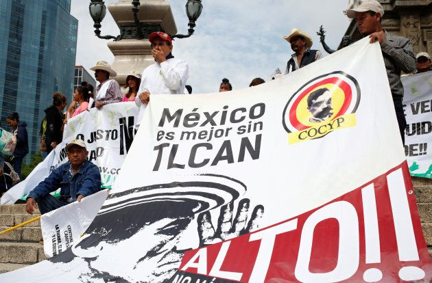 """Farmers from different states, holding a banner, take part in a march against the North American Free Trade Agreement (NAFTA) talks in front of the Angel of Independence Monument in Mexico City, Mexico July 26, 2017. The banner reads """"Mexico is better without NAFTA."""""""