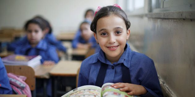 A refugee schoolchild reacts to the camera as they receive their new books on the first day of the new school year at one of the UNRWA schools at a Palestinian refugee camp al Wehdat, in Amman, Jordan, Sept. 1, 2016.