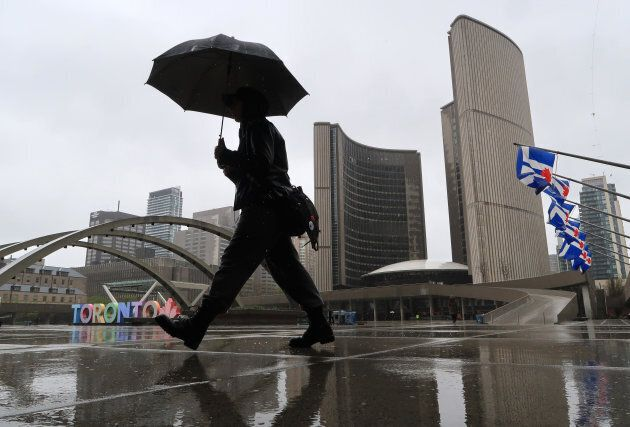 A person walks in the rain through Nathan Phillips Square in front of City Hall in Toronto,