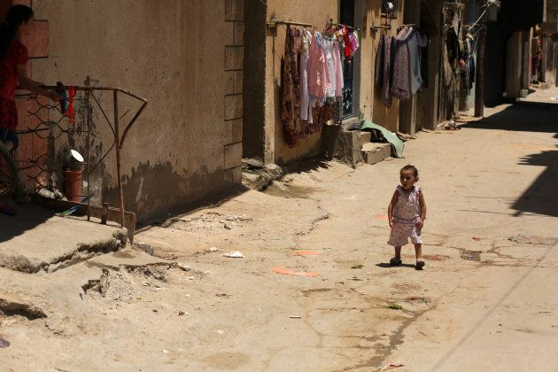 A Palestinian refugee girl walks outside her family house in the streets at al-Shati refugee camp in...