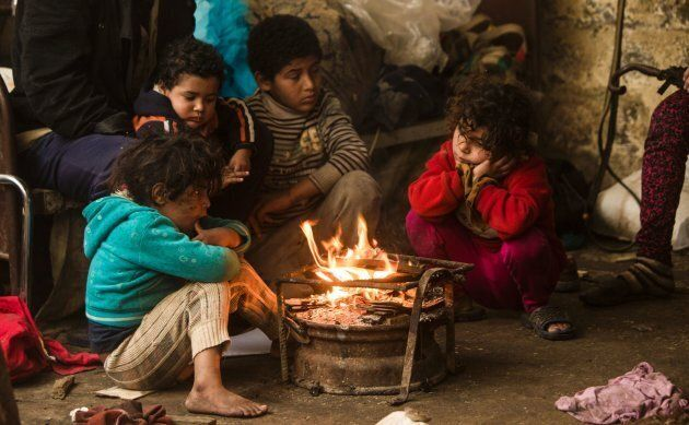 Palestinian children warm up in front of a fire in a hovel during the cold and rainy weather in the Jabalia...