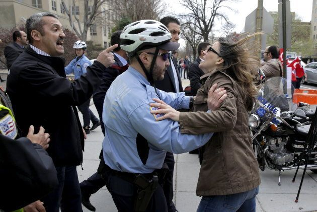 A Metropolitan police officer separates a protester (R) from a member of the Turkish security detail...