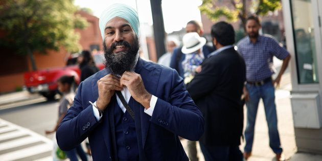 NDP leadership candidate Jagmeet Singh puts on his tie outside a meet and greet event in Hamilton, Ont....