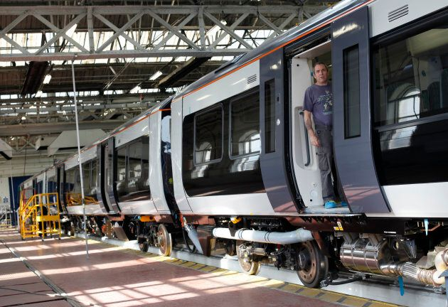 A worker stands in the doorway of a train at the Bombardier plant in Derby, central England, July 5,...