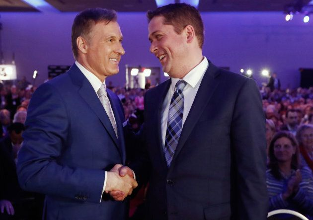 Maxime Bernier speaks with Andrew Scheer after the first results are announced during the Conservative...