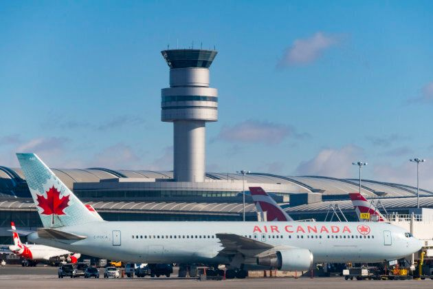 Air Canada plane in Pearson International Airport in Toronto, Ont. with the control tower in the
