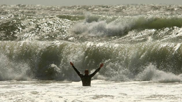A man wades into the waves of a storm surge created by the passing of Hurricane Irene at Lawrencetown...