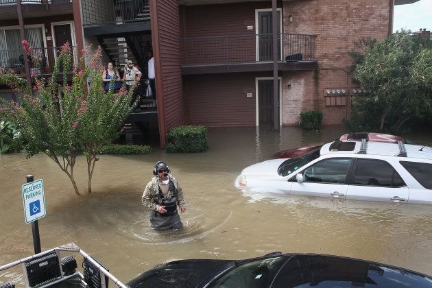 Scott Robertson helps rescue people from an apartment complex after it was inundated with water following...