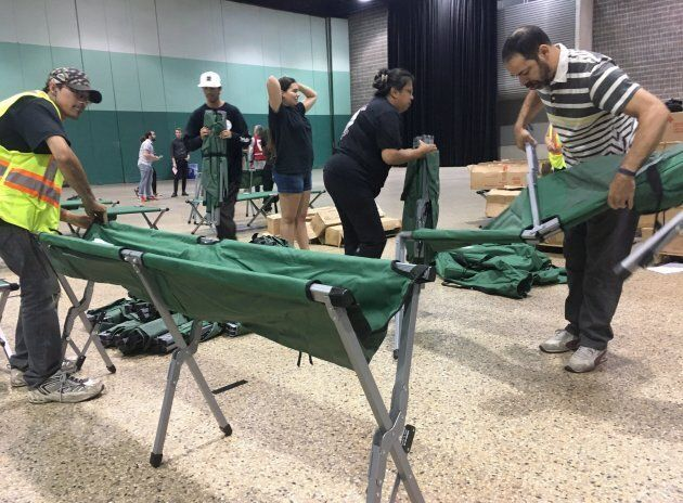 Volunteers set up cots in an emergency shelter in the Winnipeg Convention Centre for some of the 3,700...