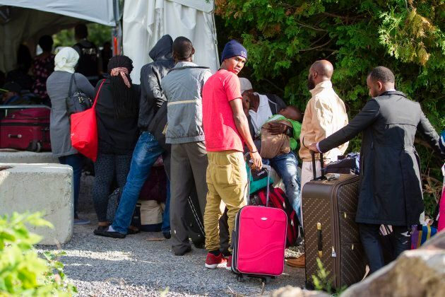 A long line of asylum seekers wait to illegally cross the Canada-U.S. border near Champlain, New York...