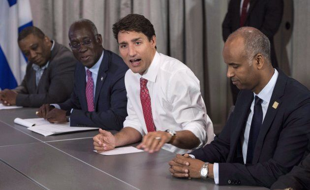 Prime Minister Justin Trudeau, MP Emanuel Dubourg, left, and Ahmed Hussen, right, Federal Minister of...
