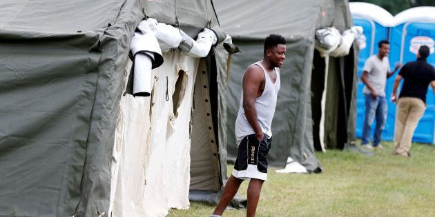 A Haitian refugee walks from his tent, one of the many set up by the Canadian Armed Forces to deal with...