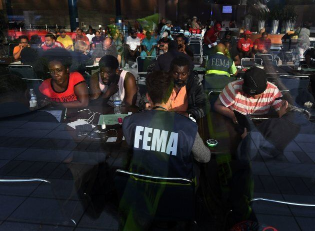 Evacuees seeking financial help consult with FEMA agents at the Convention Center which is serving as...