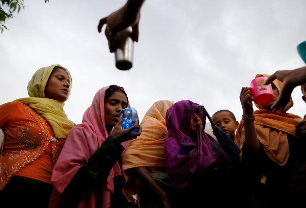 Local Bangladeshi people offer water as Rohingya refugees arrive in Teknaf, Bangladesh, September 1,