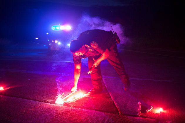 A police officer lays down a safety flare while blocking the road leading to the Arkema SA plant which...