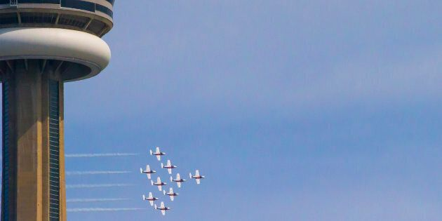 The CF Snowbirds fly past the CN Tower during the on 68th annual Canadian International Air Show during...