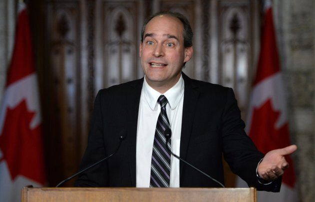 Guy Caron, then the deputy NDP finance critic, speaks at a news conference in front of the House of Commons...