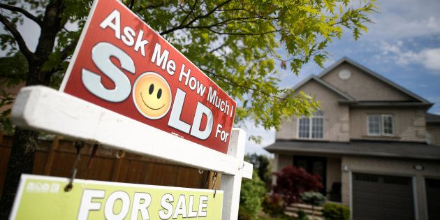 A real estate sign stands in front of a house in Vaughan, a suburb in Toronto, Canada, May 24,
