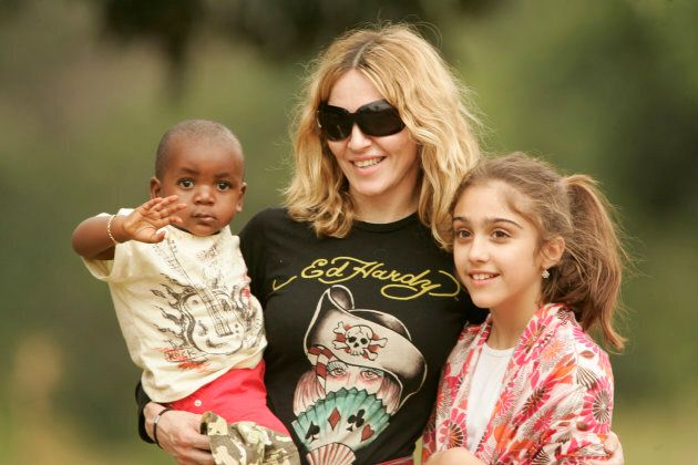 Madonna carries her adopted son David in Lilongwe on April 17, 2007. Her daughter Lourdes is to her right....