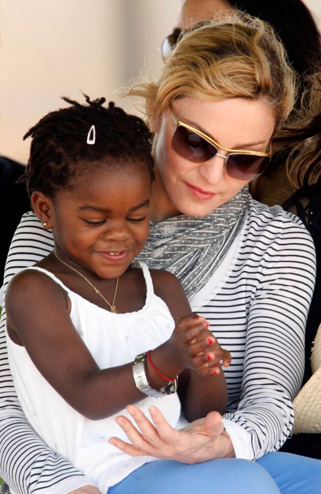 Madonna sits with her adopted daughter Mercy James in Lilongwe, April 6, 2010. REUTERS/Mike Hutchings