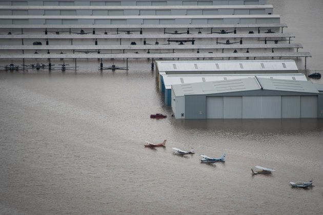 Planes are seen on the runway of West Houston Airport as flood waters surround houses and apartment complexes...