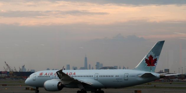 An Air Canada plane passes by the skyline of lower Manhattan in New York City as it taxis to a runway...