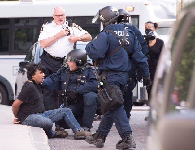 Activist Jaggi Singh sits on the sidewalk after he was arrested during an anti-racism demonstration,...