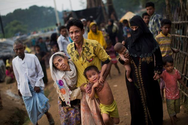 An exhausted Rohingya helps an elderly family member and a child as they arrive at refugee camp in Bangladesh...