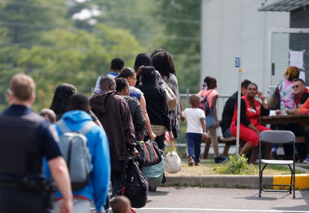 A group of asylum seekers wait to be processed after being escorted from their tent encampment to the...
