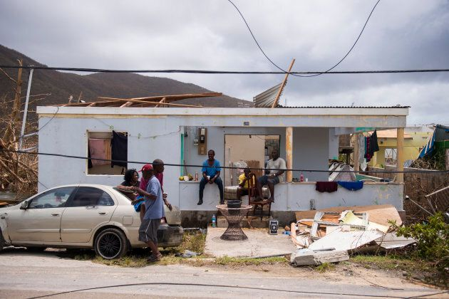 People sit among damage on Thursday on the French Carribean island of Saint-Martin, after the passage...