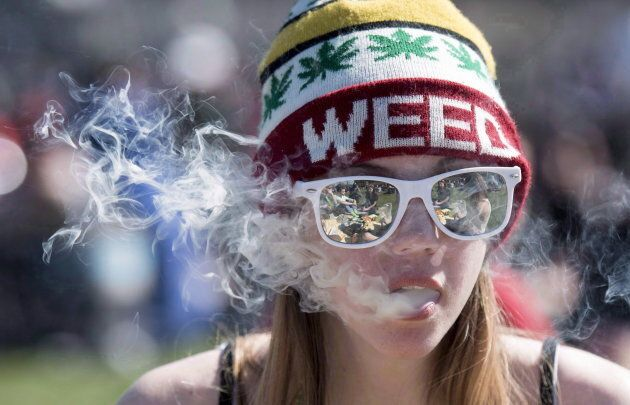A woman exhales while smoking a joint during the annual 420 marijuana rally on Parliament hill in Ottawa on April 20, 2016.