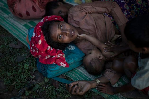 Rohingya Muslim refugees sleep under a makeshift shelter in a clearing in a forest after crossing the...