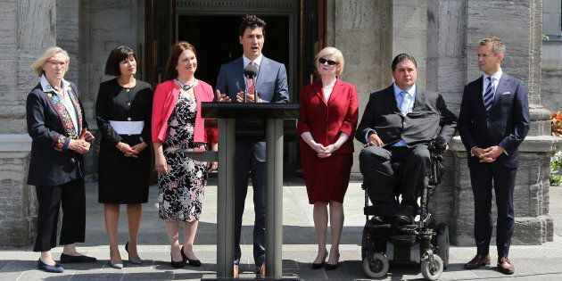 Prime Minister Justin Trudeau speaks to the press outside Rideau Hall after announcing changes to his cabinet in Ottawa, Ontario on August 28, 2017. From left, Minister of Crown-Indigenous Relations and Northern Affairs Carolyn Bennett, Minister of Health Ginette Petitpas Taylor, Minister of Indigenous Services Jane Philpott, Trudeau, Minister of Public Works Carla Qualtrough, Minister of Sport and Persons with Disabilities Kent Hehr and Minister of Veterans Affairs and Associate Minister of National Defence Seamus O'Reagan. (LARS HAGBERG/AFP/Getty Images)