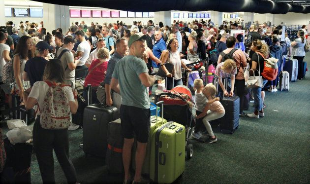 Departing passengers form a long queue to check in at Orlando International Airport ahead of the arrival...