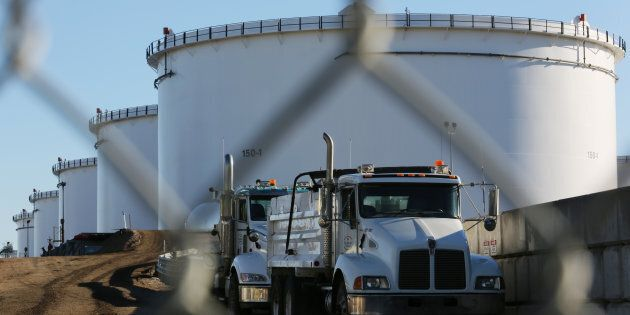 Dump trucks are parked near crude oil tanks at Kinder Morgan's North 40 terminal expansion construction...