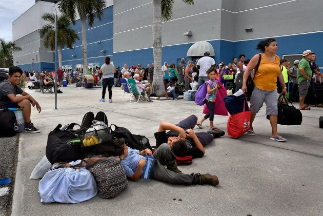 Tired families wait outside the Germain Arena in Estero, Fla. for a shelter