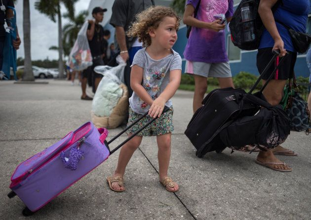 Chloe Rosenberger, 3, from Cape Coral, Fla., carries her belongings while following her brother and mother...