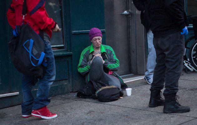 A woman sits on the ground after injecting herself with an unknown substance outside Insite, the supervised...