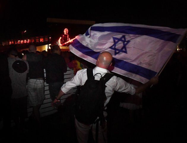 Pro-Israel supporter Paul Antey waves the Israeli flag in protest against what he says is the anti-semite political beliefs of artist Roger Waters as he performs on stage during the third day of the Desert Trip music festival at Indio, Calif. on Oct. 9, 2016.