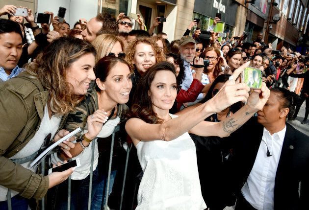 Angelina Jolie taking selfies with her fans at TIFF. (Photo by George