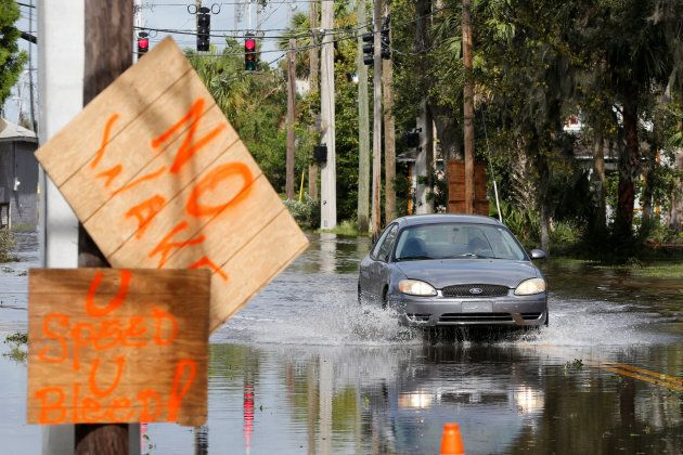 A vehicle drives on a flooded residential street in Daytona Beach, Florida after Hurricane Irma on Sept....