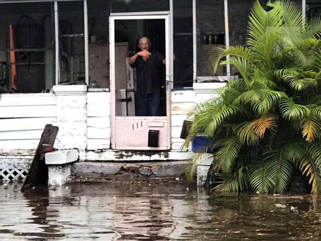 A man gestures to police officers from a flooded house after Hurricane Irma passed Daytona Beach, Florida,...