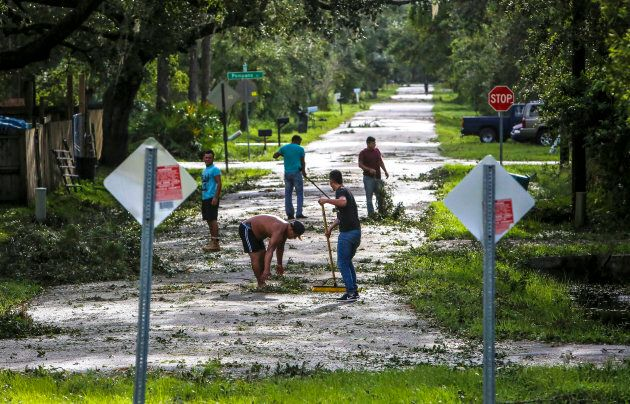 Neighbors help each other clear their road of debris on Hibiscus Road in Kissimmee, Fla. on Monday, Sept....