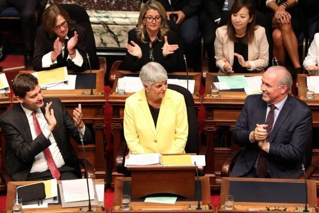 Attorney-General David Eby and Premier John Horgan clap as B.C. Finance Minister Carole James is introduced...