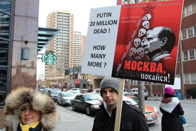 People hold placards and Ukrainian flags during a peace march from Toronto's City Hall to the Russian Consulate, in support of Ukraine on March 8, 2014, in Toronto, Ont.