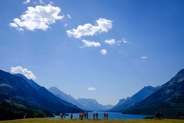 Tourists look out over Waterton Lake in Waterton Lakes National Park, Alta., Tuesday, Aug. 16,