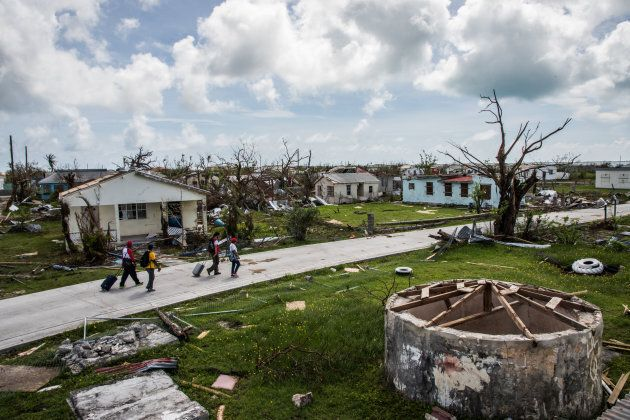 Peter Cuffy, 41, and his wife Jenita Cuffy, 40, walk behind a Red Cross crew as they look at the damages on the island of Barbuda in the aftermath of Hurricane Irma on Sunday, Sept. 24, 2017, in Codrington, Antigua and Barbuda.