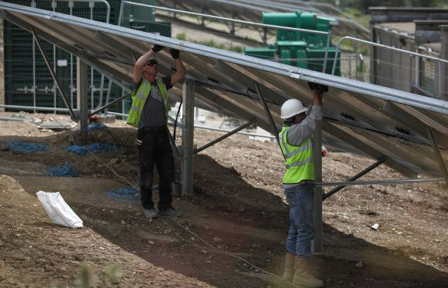 Construction workers build a solar farm.